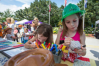 NWA Democrat-Gazette/BEN GOFF @NWABENGOFF<br /> Averie Bewley (left), 5, and sister Abigail Bewley, 8, draw faces on their rag dolls Friday, June 7, 2019, at the Benton County Historical Society and Bentonville History Museum booth during First Friday on the Bentonville square. Children could finish a rag doll, make a walking stick, or play games inspired by early settlers as part of Pioneer Explorations, a pilot project of the historical society and museum, to teach local and state history to kindergarten through 5th grade students.
