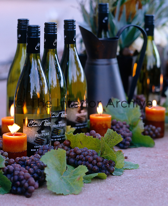 Deail of an autumnal inspired table centerpiece with lit candles grapes and wine