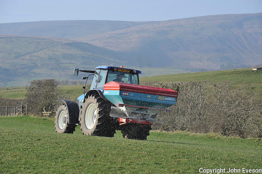 Spreading nitrogen fertilizer on pasture using a New Holland TM120 tractor and Reco Sulky DPX spreader ready for a silage crop, Chipping, Lancashire..Copyright..John Eveson,.Dinkling Green Farm,.Whitewell,.Clitheroe,.Lancashire..BB7 3BN.Tel. 01995 61280.Mobile 07973 482705.j.r.eveson@btinternet.com.www.johneveson.com