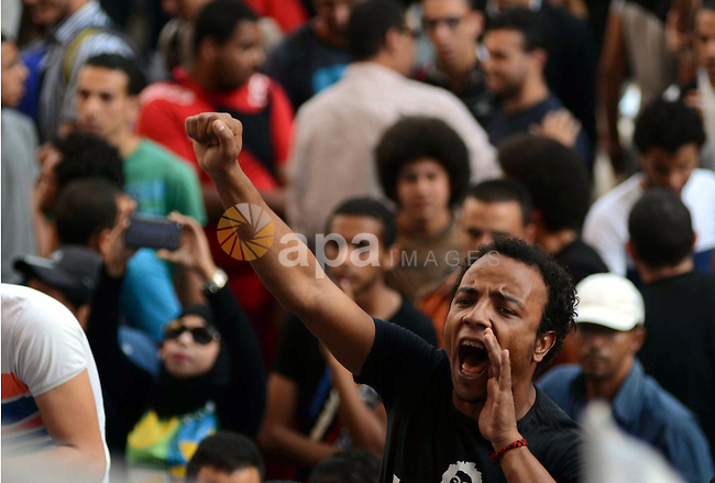 Members of the April 6 movement and liberal activists hold placards and shout slogans during a demonstration outside the Journalists Syndicate, in Cairo on April 30, 2014. The April 6 youth movement has vowed to keep operating after the Court of Urgent Matters banned on Monday all activities by the youth movement, which played a significant role in revolutions against former presidents Hosni Mubarak and Mohamed Mursi. The court also seized its headquarters and ordered a freeze on April 6′s assets. Photo by Mohammed Bendari