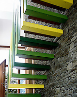 A triple height stairwell is a successful marriage of old and new with a bold green contemporary staircase contrasting with natural slate and stone from the surrounding area.