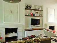 A matching pair of fireplaces in the living room are linked by open bookshelves