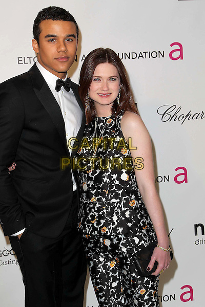 guest & Bonnie Wright.The 21st Annual Elton John AIDS Foundation Academy Awards Viewing Party held at The City of West Hollywood Park in West Hollywood, California, USA..February 24th, 2013.oscars half length white black orange print pattern jumpsuit clutch bag sleeveless tuxedo white shirt bow tie.CAP/ADM/KB.©Kevan Brooks/AdMedia/Capital Pictures.