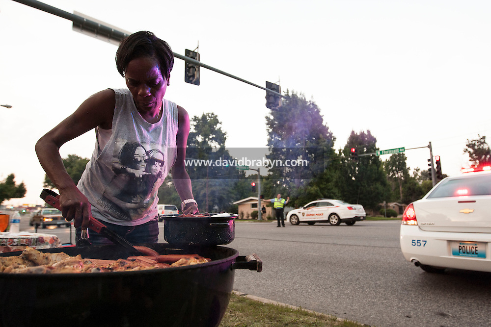 HSUL 20140818 United States, Ferguson, MO. Peraisee Moore barbecues food for passers-by alongside a police road barrage on West Florissant Avenue in Ferguson, Missouri, on August 18, 2014. Photographer: David Brabyn