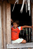 Porto Seguro, Bahia State, Brazil. Smiling Pataxo Indian boy looking out of his house; near Coroa Vermelha.
