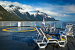 Alaska Marine Highway System sailing through Lynn Canal, Inside Passage, SE Alaska on a sunny day.  Snow capped mountains are towering over the ocean. Deck chairs in the foreground.