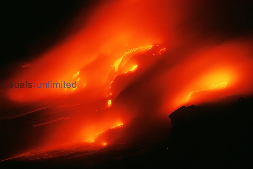 Hot molten lava entering the Pacific Ocean at night, creating new land and massive steam, Hawaii Volcanoes National Park, Kilauea, Big Island, Hawaii.