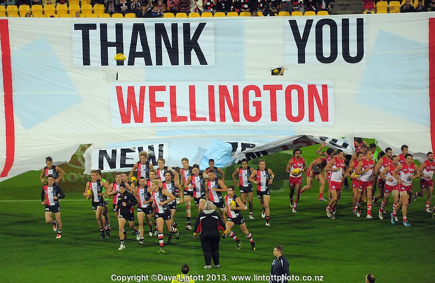The teams run through a commemorative banner at the start of the Australian Rules Football ANZAC Day match between St Kilda Saints and Sydney Swans at Westpac Stadium, Wellington, New Zealand on Thursday, 24 May 2013. Photo: Dave Lintott / lintottphoto.co.nz