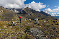 Hiker and tent camp in the Brooks Range., Gates of the Arctic National Park, Alaska