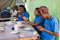 Haiti, Port-au-Prince. Artisan business, Papillon. Produce ceramics, jewelry, t-shirts. Over 300 women on payroll (men work her as well), making about $15 a day. Women making paper beads from recycled paper.