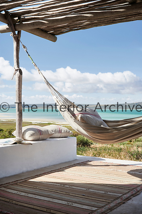 A hammock is suspended on a covered terrace affording a view to the beach.