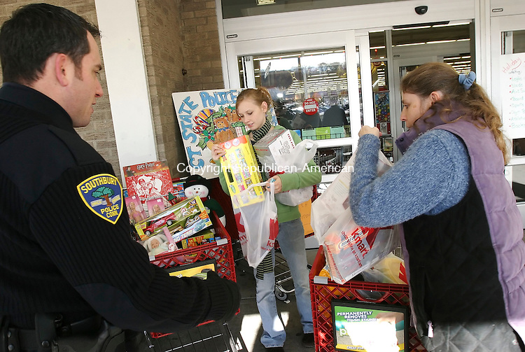 SOUTHBURY, CT 11/23/07- 112307BZ08- From left- Southbury Police Officer Dan Norck accepts toys from Jessica Varley and her mother Heidi Finch, of Roxbury, during the police force's annual post-Thanksgiving toy drive outside the KMart in Southbury Friday.<br /> Jamison C. Bazinet Republican-American