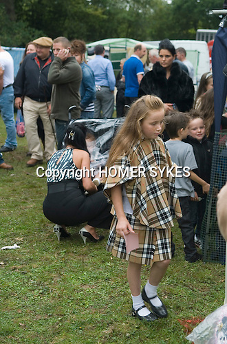 Barnet Gypsy Horse Fair Hertfordshire UK. Chav gypsy girl wearing a Burberry style matching check cape and shirt. Her mother seen behind with pram.