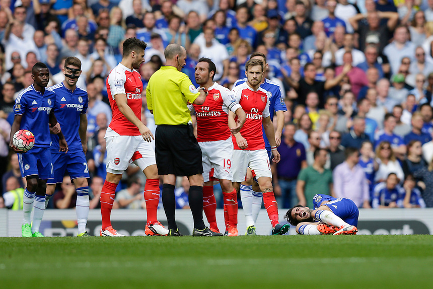 Chelsea's Cesc Fabregas lies on the ground in pain after a challenge by Arsenal's Santi Cazorla for which he receives a second yellow card, and therefore sending off, from referee Mike Dean<br /> <br /> Photographer Craig Mercer/CameraSport<br /> <br /> Football - Barclays Premiership - Chelsea v Arsenal - Saturday 19th September 2015 - Stamford Bridge - London<br /> <br /> &copy; CameraSport - 43 Linden Ave. Countesthorpe. Leicester. England. LE8 5PG - Tel: +44 (0) 116 277 4147 - admin@camerasport.com - www.camerasport.com