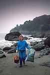 Environmental Volunteer woman carrying trash during coastal clean up day Muir Beach Marin County Coast California Women picking up trash off beach during Coastal Clean-up day, Muir Beach, Marin County coast, California