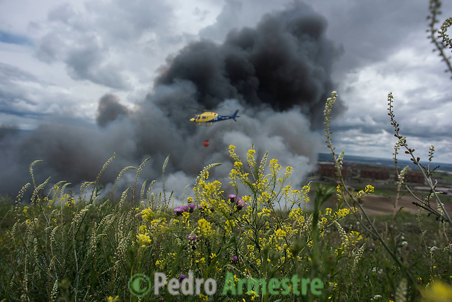 A helicopter drops water over the tyres burning in an uncontrolled dump near the town of Sesena, after a fire broke out early on May 13, 2016. A huge waste ground near Madrid where millions of tyres have been dumped was on fire today, releasing a thick black cloud of toxic fumes that officials worry could harm residents nearby.  © Pedro ARMESTRE