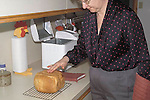 Removing fresh baked bread from bread machine testing for doneness