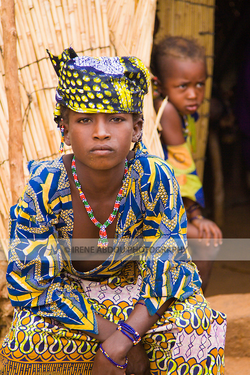 A young Fulani woman in the tiny village of Bele Kwara sits on a stool in front of her house, as a young girl glances out from the doorway.