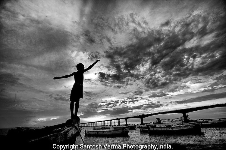 A young boy from the fishing village stretches out his arms as if to measure the vast landscape of the sea, sky and one of India' longest, crucial bridge in South India. Photograph © Santosh Verma