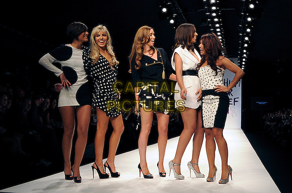 THE SATURDAYS - FRANKIE SANDFORD, MOLLIE KING, UNA HEALY, ROCHELLE WISEMAN & VANESSA WHITE.The Fashion For Relief Haiti 2010 show for London Fashion Week Autumn/Winter 2010 at Somerset House, London, England..February 18th, 2010.LFW catwalk runway full length black dress mini navy white polka dot profile laughing .CAP/CAS.©Bob Cass/Capital Pictures.