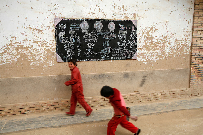 IFADHuinin_058-060  Students walk past a blackboard describing different student assistance schemes at the Linfang Elementary School in Linfang Village, Zhaisuo Township, Huinin County, Gansu Province on 20th March 2006.