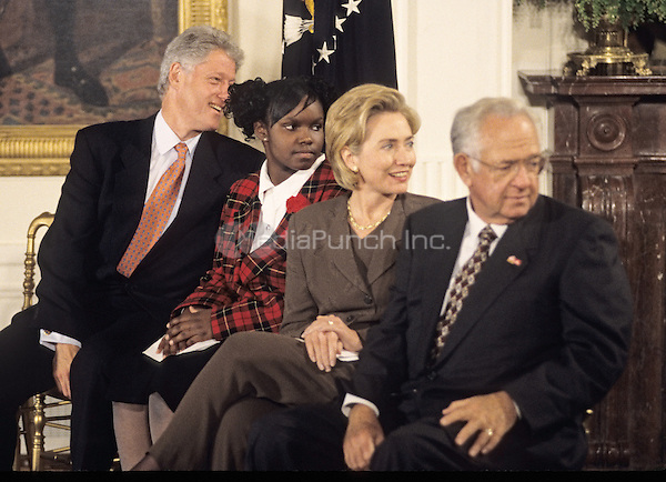 United States President Bill Clinton and first lady Hillary Rodham Clinton host an event in the East Room of the White House advocating expanded use of the internet to place adoptions in Washington, D.C. on November 24, 1998.  From left to right: President Clinton; Charday Mays;  the first lady; and Dave Thomas, founder of Wendy's.<br /> Credit: Ron Sachs / CNP/MediaPunch