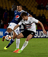 BOGOTÁ - COLOMBIA, 15-08-2018: John Duque (Izq.) jugador de Millonarios (COL), disputa el balón con Enrique Borja (Der.) jugador de General Díaz (PAR), durante partido de vuelta entre Millonarios (COL) y General Díaz (PAR), de la segunda fase por la Copa Conmebol Sudamericana 2018, en el estadio Nemesio Camacho El Campin, de la ciudad de Bogotá. / John Duque (L) player of Millonarios (COL), fights for the ball with Enrique Borja (R) player of General Diaz (PAR), during a match of the second leg between Millonarios (COL) and General Diaz (PAR), of the second phase for the Conmebol Sudamericana Cup 2018 in the Nemesio Camacho El Campin stadium in Bogota city. VizzorImage / Luis Ramirez / Staff.