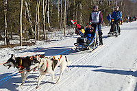 Lisbet Norris and team run past spectators on the bike/ski trail during the Anchorage ceremonial start during the 2014 Iditarod race.<br /> Photo by Britt Coon/IditarodPhotos.com