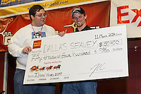 Dallas Seavey gets his winner's check from Scott A. Johnson with Wells Fargo Bank Alaska at the musher 's finishers banquet in Nome on Sunday March 16 after the 2014 Iditarod Sled Dog Race.<br /> <br /> PHOTO (c) BY JEFF SCHULTZ/IditarodPhotos.com -- REPRODUCTION PROHIBITED WITHOUT PERMISSION