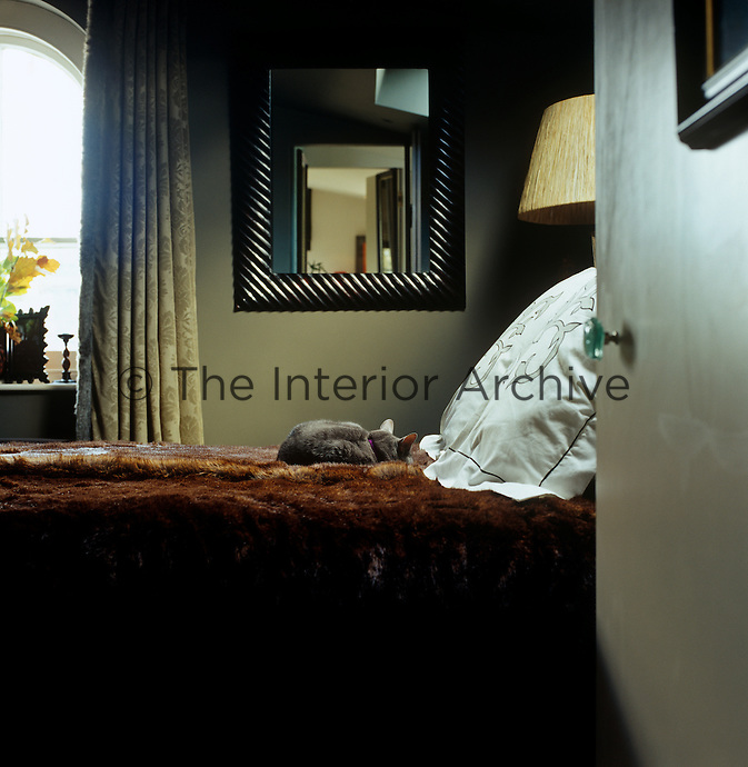 In the master bedrooom a luxurious fur throw creates an instant air of opulence