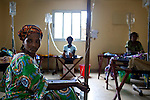 Assitou, left, and a roomful of women receive fluids for rehydration at Donka Cholera Treatment Center in Conakry, Guinea, Aug. 16, 2012. Médecins Sans Frontières is responding to a cholera outbreak in Guinea, which is affecting coastal areas and inland. Two emergency MSF cholera treatment centers in Conakry are receiving around 60 new cases per day, and a third treatment center opened over the weekend.
