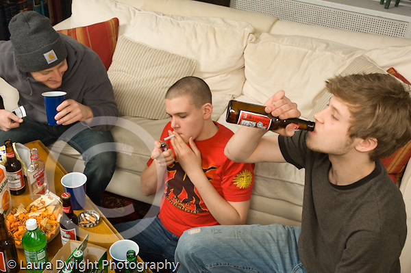Teenage boys smoking cigarettes and drinking alcohol