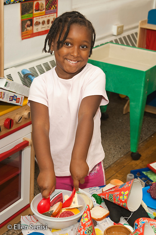 MR / Schenectady, New York. Fulton Early Childhood Education Center (urban public school early childhood education center). Pre-K classroom. Portrait of student (girl, 5) smiling while playing with pretend food in house corner at free playtime. ID: AI-gPd. MR: Cal10 ©Ellen B. Senisi
