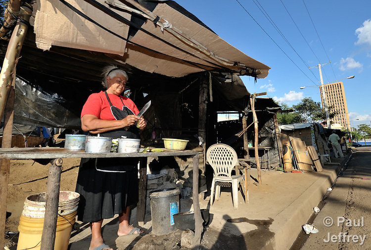 A woman prepares a meal in a camp in Managua of some 3,000 former banana workers who have been poisoned by Nemagon (dibromochloropropane). Camped out across the street from the Nicaraguan National Assembly, the workers are pressuring the government to provide health care and support their legal actions against US companies which manufactured and used the pesticide. Nemagon is considered a risk factor for cancer, kidney failure, acute respiratory disease, heart attack, sterility, muscular atrophy, skin complaints, and other health problems. The tall building in the rear is the National Assembly.
