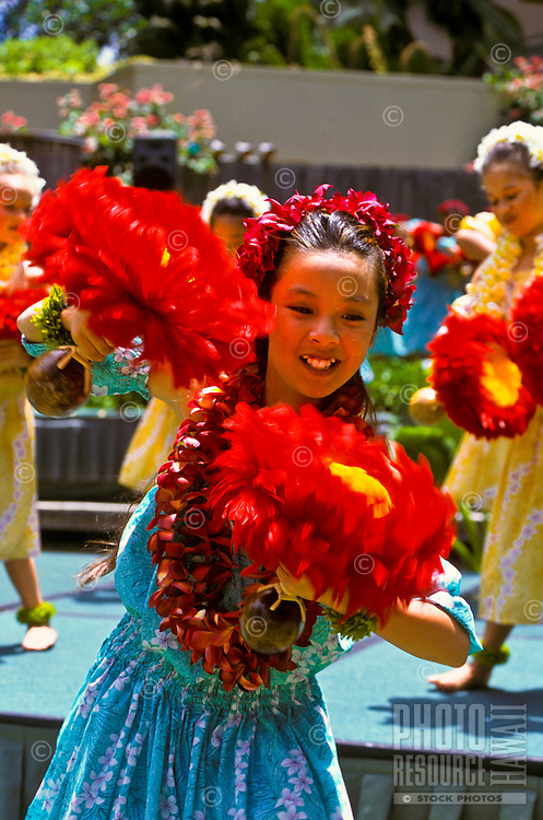 young hula dancers with feathered uli uli (gourd rattles) and plumeria leis; Lei Day performance at Hilton Hawaiian Village Hotel
