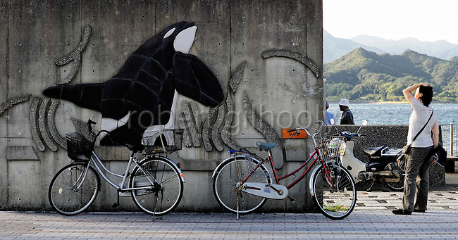 A woman looks at a mural of a whale outside the whaling museum in Taiji, Japan on 10 September  2009.  .Photographer: Robert Gilhooly