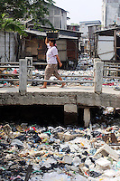 A woman crosses a bridge over a heavily polluted river in a Jakarta slum.<br />