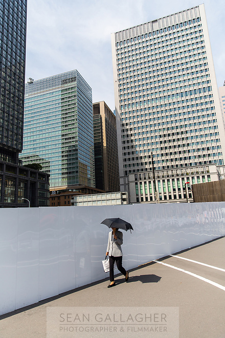 A woman with an umbrella walks through a business district in central Tokyo.