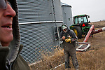 Mike Nelson, left, and Mark Nelson watch as corn is loaded into a truck on Wednesday, November 30, 2011 in Webster City, IA.