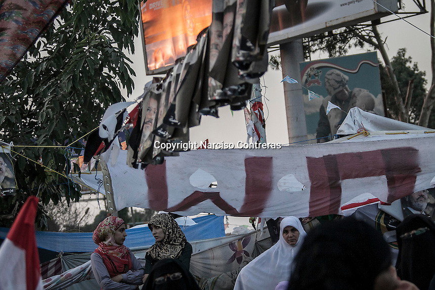 In this Wednesday, Jul. 24, 2013 photo, female supporters of the ousted president Mohammed Morsi await to break up their fast in the nearby streets to Al-Rabaa mosque in the Nasr City neighbourhood of Cairo. (Photo/Narciso Contreras).