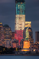 Two symbols of freedom, the Statue of Liberty and the Freedom Tower (One World Trade Center), are illuminated at twilight in New York City.  The Freedom Tower, lighted in the red, white, and blue colors of the American flag, is scheduled for completion in 2013.