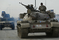 Iraqi tank from the 1st company, 1st armour battalion of the 1st mechanized Iraqi Army Brigade cruises while conducting  patrols, check points and observation posts on code name route Michigan, the main road of Ramadi in the week during the national election on TUE Dec 13 2005 in Ramadi, Iraq. 1st company is part of the first armor battalion of the New Iraqi Army. it has started its training in January 2005. after 50 days their 35 russian and chinese built T 55 tanks begun conducting operations under the guidance of a US military adivisor team. in April 2005 they patrolled in the Abu Ghraib area concluding their first significant mission. While these old tanks are rolling on the ramadi streets more modern T72s are getting ready to become fully operational in Taji, their main base. the Iraqi army wanted to show their power in ramadi during the Dec 15 elections displaying their new armour company. but like all the other Iraqi forces they are not going to secure the polling sites, staying in the rear with the rest of the iraqi and coalition forces. T 55s are very old tanks. production begun in the late 50s to the late 70s. athough obsolete many countries still use the T55 as their main heavy armoured combat vehicle. slow, heavvy and with very little room for the crew it suffers from many mechanical problems constantly challenging the iraqi mechanics and engineers.