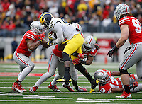 A herd of Buckeye defenders brings down Michigan Wolverines quarterback Devin Gardner (98) during the 4th quarter of the NCAA football game at Ohio Stadium on Nov. 29, 2014. (Adam Cairns / The Columbus Dispatch)