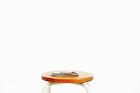 Small amount of US banknotes on stool, white background
