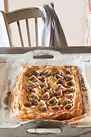 A delicious fig tart with ricotta cheese, almonds and honey served on a rustic wooden tray