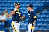 Michigan Wolverines designated hitter Drew Lugbauer (17) high fives pitcher Jimmy Kerr (15) after scoring a run during the second game of a doubleheader against the Canisius College Golden Griffins on February 20, 2016 at Tradition Field in St. Lucie, Florida.  Michigan defeated Canisius 3-0.  (Mike Janes/Four Seam Images)