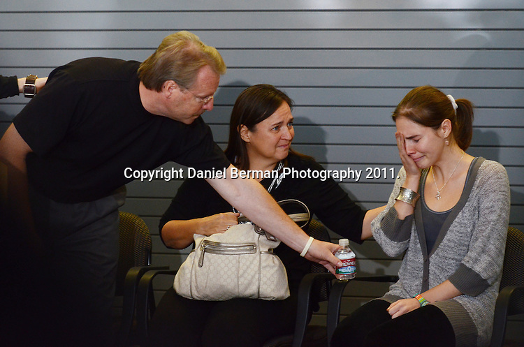 Amanda Knox is comforted by her father, Curt Knox, and mother, Edda Mellas, as she is overcome with emotion after acknowledging the waiting crowd and enormous media presence upon her arrival in the United States at Seattle-Tacoma International Airport in Seattle Tuesday, October 4. Knox's murder conviction was overturned by an Italian appellate court after spending four years in prison in Italy. Photo by Daniel Berman/www.bermanphotos.com