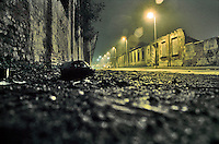 Milano, quartiere Bovisa, periferia nord. Una bottiglia a terra in via Bellagio, strada in stato di degrado che passa lungo vecchie fabbriche in disuso --- Milan, Bovisa district, north periphery. A bottle on the ground in Bellagio street, a road in a state of decay that runs along old disused factories