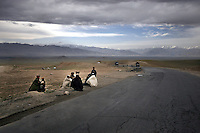 Afghans sit by the roadside, on the way to Kabul from Bagram.
