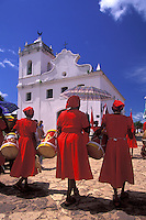 Festa do Divino ( Divino Party ), Alcântara, State: Maranhão, Brazil. Black elderly women, afro-descendant aged women, cultural traditions, red clothings, percussion instruments, musical instruments ( drums ), sunny day, church.